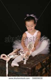 Cute Little Brunette Girl Trying On Ballet Pointe Shoes Stock Photo